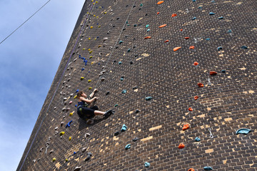 woman climbs up an artificial rock wall - secured with a rope against falling