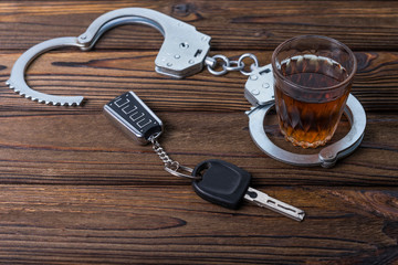 Alcohol, handcuffs, keychain, car keys on the background of a wooden table. driving under the influence. violation of law.