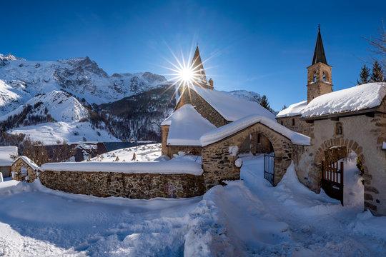 La Grave, Hautes-Alpes, Ecrins National Park, Alps, France: The local village of La Grave and its church with La Meije mountain peak in winter