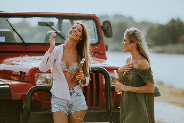 Attractive young women standing by a convertible car