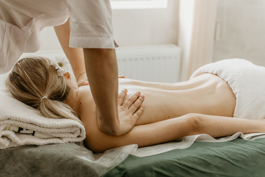 Masseur doing back massage to young woman.