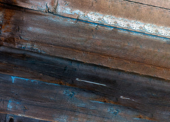 Old wooden planks. Blue and brown dry wood. Planks painted in blue paint. Peeling paint. Cracks. Natural Texture.