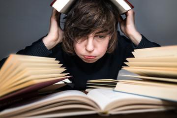 Studentin sitzt überfordert vor ihren Lehrbüchern