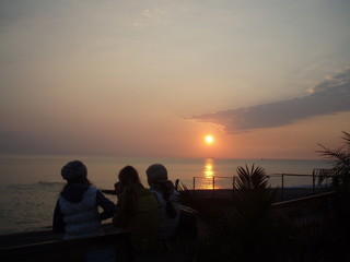 silhouettes of girls watching the sunset on the sea