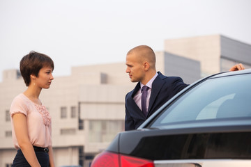 Young couple in conflict talking beside a car on city street