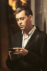 Young handsome business man using cell phone on city street