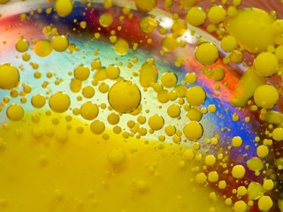 Scores of yellow paint drops on multicolour background. Close up macro shot. Blurred background. Selective soft focus. Colorful abstract universe. Glittering yellow spheres