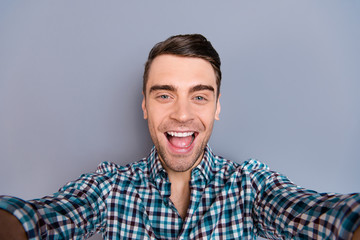 Close up photo attractive amazing macho he him his man arm hand telephone smart phone make take selfies mouth open wearing casual plaid checkered shirt outfit isolated grey background