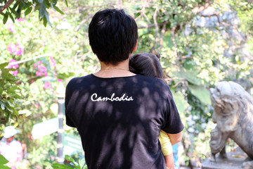 "Backside of man in black T-shirt with white text ""Cambodia"" and carry children."