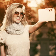 Young fashion woman taking a selfie with digital tablet computer outdoor