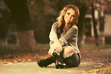 Happy young fashion woman in ripped jeans sitting on sidewalk