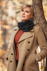 Young fashion woman in beige coat walking in autumn park