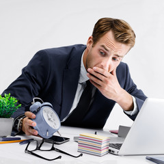 Busy businessman looking at alarm clock