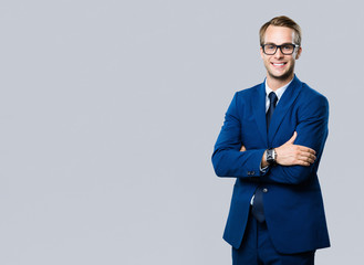 young businessman in glasses, against grey