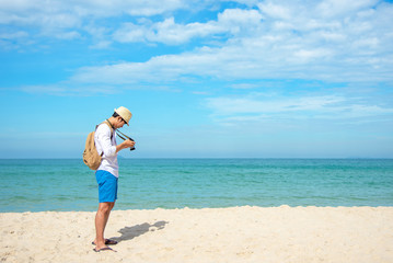 Summer Day.  Happy smiling caucasian tourist asian young man holding camera for take a photo check in on the beach. Summer and Travel Concept.