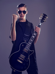 Fifteen years old guitarist with a  black electric guitar.