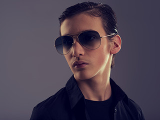Handsome fifteen years old guy in a black stylish sunglasses.
