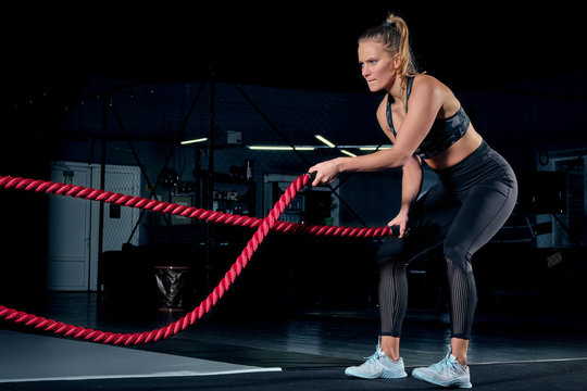 Athlete working out with battle ropes at cross gym.