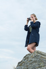 A girl tourist stands on a rock over a cliff in the Carpathians and photographs the landscape.