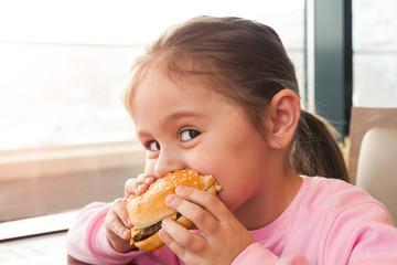 Foto op Canvas Kruidenierswinkel Little child eating a hamburger in the cafe