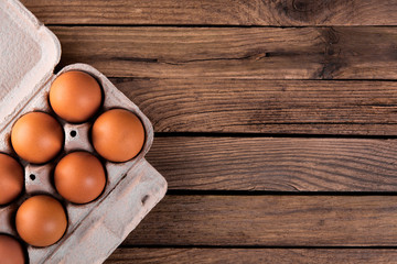 raw chicken eggs in egg box on wooden background