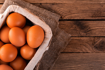 close-up of raw chicken eggs in basket on wooden background