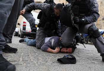 Israeli police officers detain a Palestinian protestor during scuffles outside the compound housing al-Aqsa Mosque in Jerusalem's Old City