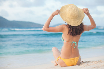 back view of long haired woman in bikini and straw hat relaxing on tropical beach. La Digue, Seychelles