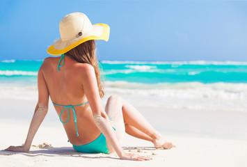 long haired woman in bikini and straw hat lying on tropical beach