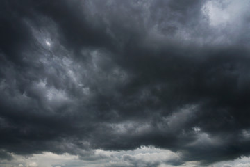 Dark, grim, stormy, rainy sky with rays of light. Scary hurricane clouds. Natural element. Stock Photo for your design