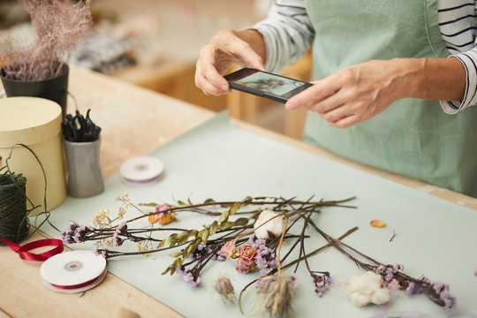 Closeup of unrecognizable woman taking mobile photo of flower composition in art studio, copy space