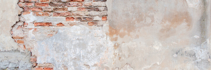 Old grungy red brick wall with peeled white beige stucco banner background. Vintage retro plaster wall with dirty cracked scratched texture background