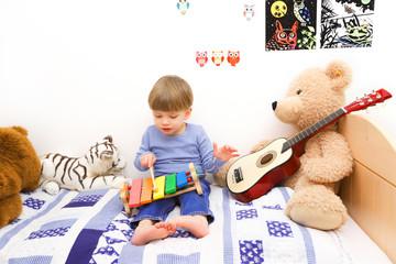 Ein dreijähriger Junge spielt auf einem Holzxylophon