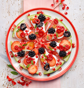 Watermelon pizza, vegetarian, fruit  pizza with creamy natural yogurt and fresh fruits  on a plate, on a white wooden table, top view. Healthy and gourmet dessert or snack,  healthy eating concept