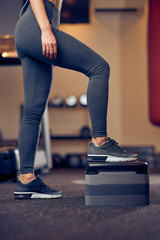 Caucasian blonde woman exercises on steps . Gym interior, healthy lifestyle concept.