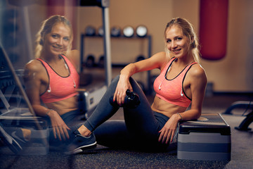 Smiling woman drinking water and resting after exercises while sitting on the floor. Gym interior.