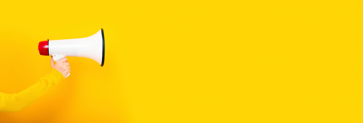 megaphone in hand on a yellow background, panoramic image, attention concept announcement