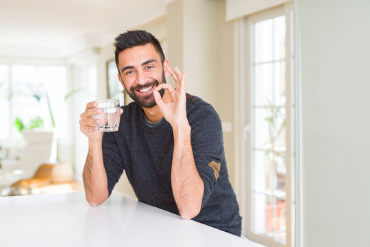 Handsome hispanic man drinking a fresh glass of water doing ok sign with fingers, excellent symbol