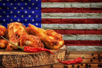 Chicken wings with red hot chili pepper, salt and peppercorn on wooden table. USA flag's image in background.