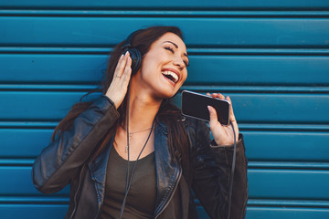 Young woman enjoys music on the street against blue wall