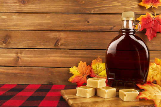Maple syrup bottle on a wooden plank. Maple leaves in decoration. Copy space for your text.