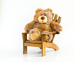 cuddly teddy bear sitting on a brown Adirondack chair isolated on white