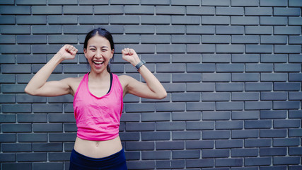 Healthy beautiful young Asian runner woman feeling happy smiling and looking to camera after running on street in urban city. Lifestyle fit and active women exercise in the city concept.