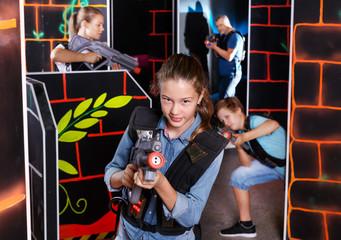 Teen girl with laser pistol on dark labyrinth