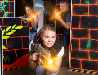 Portrait of young woman holding laser gun  in arena, playing las
