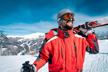 Portrait of young smiling skier standing on top of mountain while holding skis