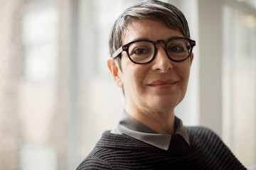 Portrait of smiling businesswoman wearing eyeglasses while standing against window in office