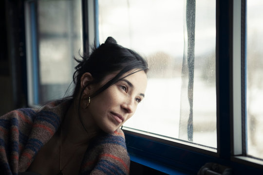 Thoughtful woman wrapped in blanket looking through window while sitting at home