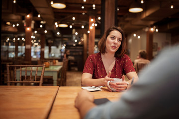 Cropped image of businessman discussing with female colleague in coffee shop