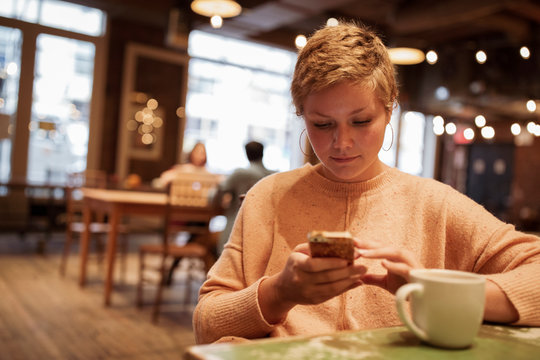 Confident businesswoman with short hair using smart phone while sitting in coffee shop